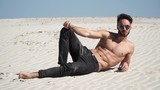 Beautiful guy sitting model looks and pours sand from hands