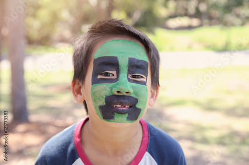 Young boy with fun green and black face painting