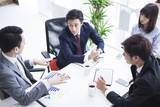 Four young businessmen are meeting in a bright office
