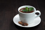hot chocolate with mint in a cup on a dark wooden background