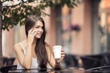Young Beautiful Woman In Coffee Shop Talking On Phone.