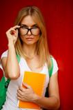 Student adjusts glasses on empty background
