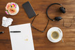 Desktop scene with notes, coffee stain, coffe, headphones and music shot from above