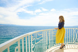 Woman by the sea. Full length shot of an elegant middle aged lady standing at balcony by the ocean and enjoying the view.