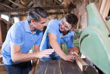 Carpenter Teaching Apprentice How To Use Circular Saw