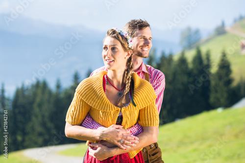 Poster Paar in Tracht im Urlaub auf Alpen Berggipfel
