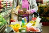 Woman using mobile phone while shopping