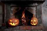 two Halloween pumpkins at the fireplace with fire
