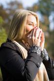 junge blonde Frau mit Taschentuch im Herbst
