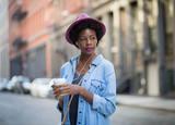 Fototapety Fashionable African American woman listening to music and enjoyi