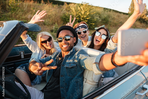 Happy young people taking selfie with smartphone in the car