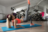Woman make pilates exercise lying on floor in gym