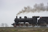Old steam locomotive running on rails - 121944732