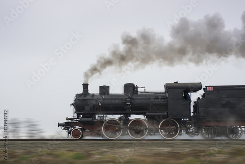 Old steam locomotive running on rails Poster