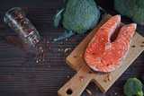 Raw salmon steak with sea salt, pepper and broccoli