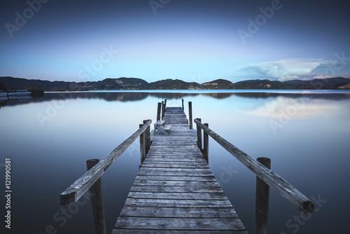 Drewniany molo lub jetty na błękitnym jeziornym zmierzchu i nieba odbiciu dalej