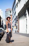 Portrait of fashionable woman walking on city street - 121994517