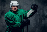 Hockey player in protective clothes holds playing stick.