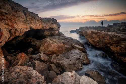 Catching the sunrise / Magnificent sea sunrise with a silhouette of a woman with camera at the rocky coast near Shabla, Bulgaria