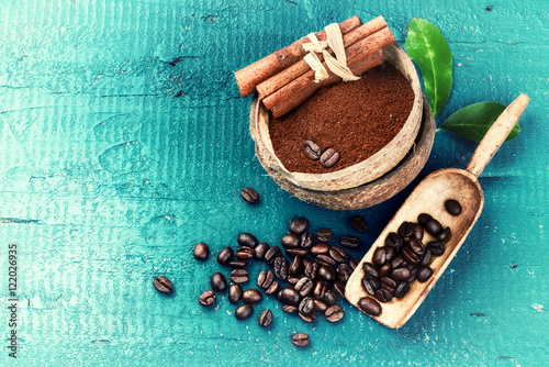 Roasted coffee beans with ground coffee and cinnamon sticks