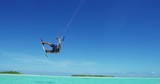Young man kitesurfing in tropical blue ocean, extreme sport slow motion