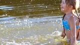 Little girl waves a hand, splashing water in a reservoir, in different directions, laughs.