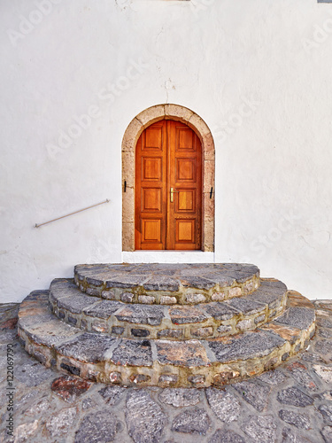 Greece, vintage wooden arched door and round stairs entrance