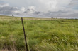 Barb wire fence around Farm with storm clouds