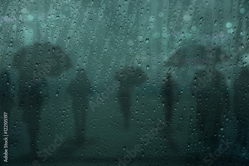 Blurred silhouette People walk in the Rain with Umbrella on the Street at night, Poster