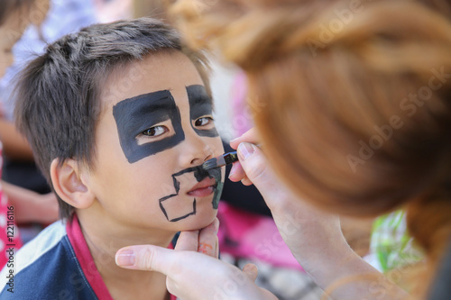 Young boy getting face painted