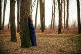 Lonely woman standing in forest in winter