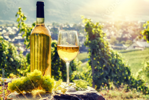 Papiers peints Jaune de seuffre Bottle and full glass of white wine over vineyard background