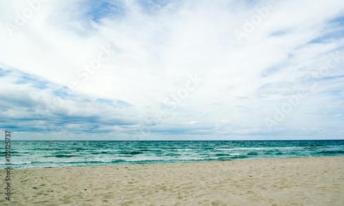 Dark green autumn sea, cloudy sky and a sand beach - 122125737