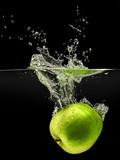 Green apple falling in water on black background