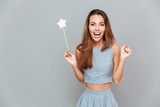 Happy amazed young woman holding magic wand - 122129302