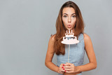 Pretty cute young woman blowing on birthday cake props