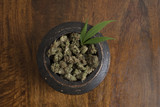 Cannabis sativa flower buds and leaf in wooden pot, on wooden background