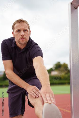 Poster sportler dehnt seine wade vor dem training