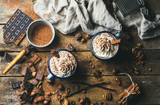 Hot chocolate with whipped cream, nuts and cinnamon in enamel mugs with ingredients around on rustic wooden background, top view, horizontal composition