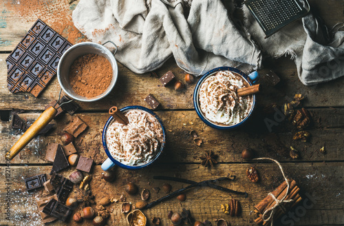 Tuinposter Chocolade Hot chocolate with whipped cream, nuts and cinnamon in enamel mugs with ingredients around on rustic wooden background, top view, horizontal composition
