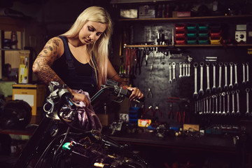 Blond woman mechanic working in a motorcycle workshop