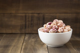 Raw pinto beans in bowl on wooden table