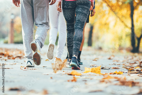 Foto op Canvas Jogging Group of friends in sportswear walking at the park on beautiful day.Autumn concept.Rear view.Only legs are visible.