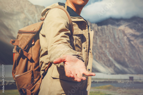 Young travel man lending a helping hand in outdoor mountain scenery Poster