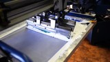 An industrial silkscreening press machine in a factory.