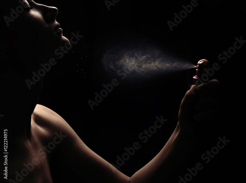 Young woman with spraying perfume on black background