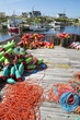 Brightly colored buoys and ropes sit piled next to lobster traps on a deck on the shore of a fishing village in Peggy's Cove, in Halifax, Nova Scotia, Canada