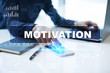 """Businessman is working in office, pressing button on virtual screen and selecting """"Motivation"""". Business concept."""