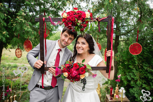 Wedding portrait. Bride and groom smiling and posing with frame. Red wedding