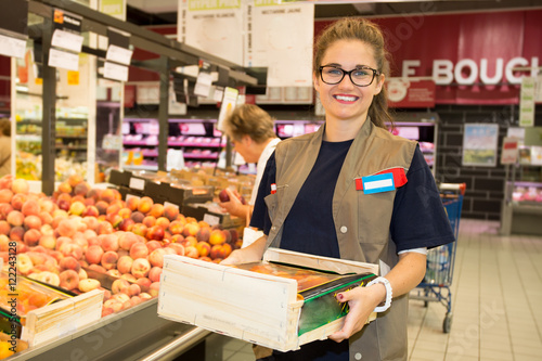 Happy female worker in supermarket holding a large wooden tray